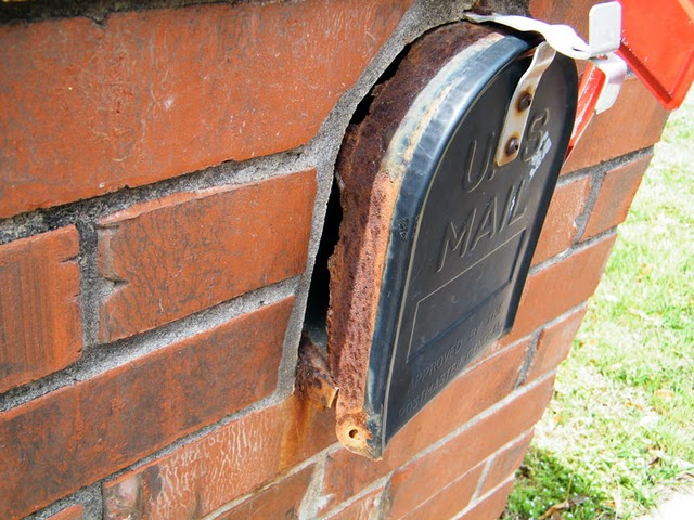 Image of a rusted out mailbox container encased within sound brick.