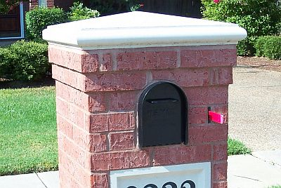 A Cast Capstone tops a Beautiful Brick Mailbox Design