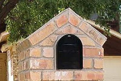 A brick mailbox with a steeple top application of bricks
